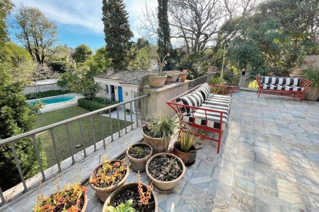 La vista del jardín desde uno de los balcones, con sillones de hierro y almohadones a rayas.