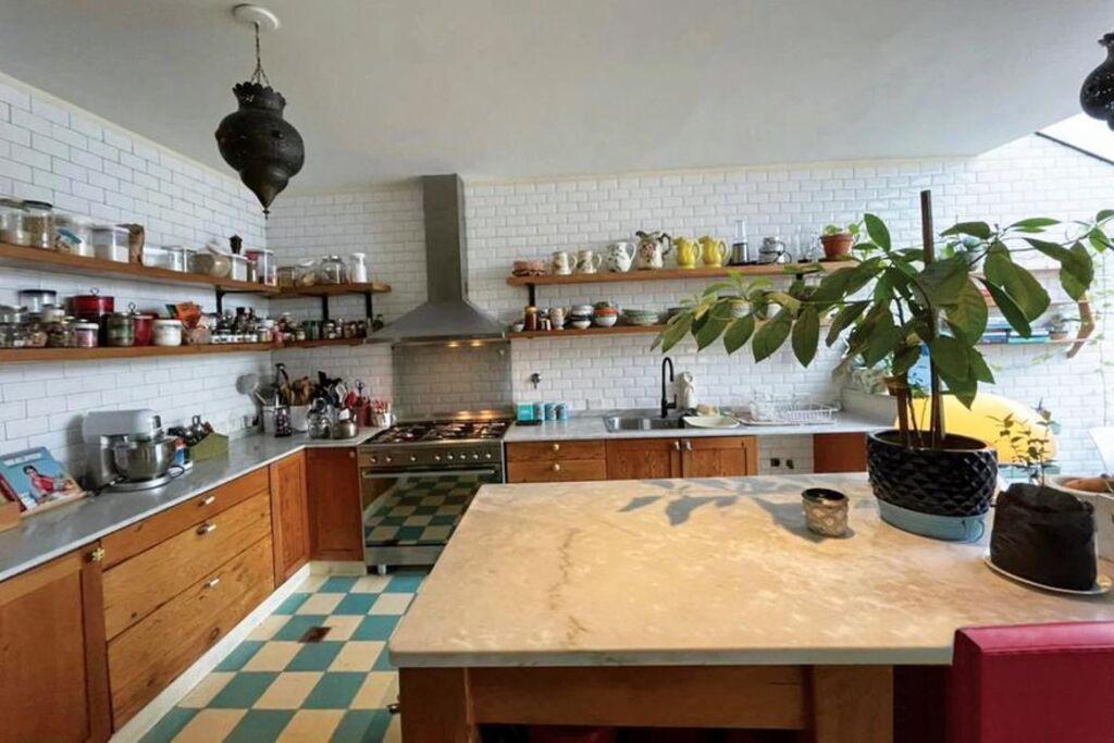 """La cocina tiene azulejos """"Subway"""", pisos calcáreos y una isla central con tapa de mármol."""